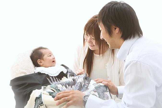 赤ちゃんを見つめるお母さんとお父さんの写真